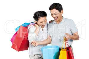Older asian couple with shopping bags