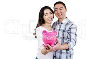 Portrait of cheerful couple holding piggy bank
