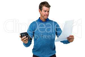 Shocked man holding calculator and paper