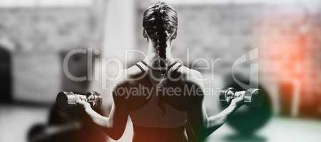 Composite image of rear view of braided hair woman lifting dumbb