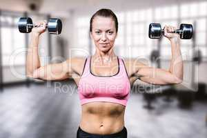 Composite image of portrait of smiling woman lifting dumbbells