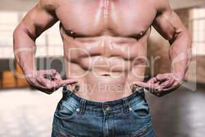 Composite image of midsection of shirtless man pointing at abs