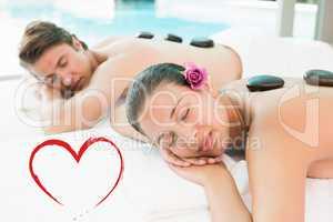 Composite image of couple enjoying stone massage at health farm