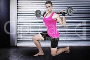 Composite image of sporty female bodybuilder lifting barebell