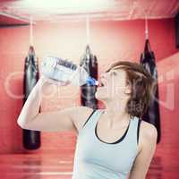 Composite image of pretty brunette drinking water