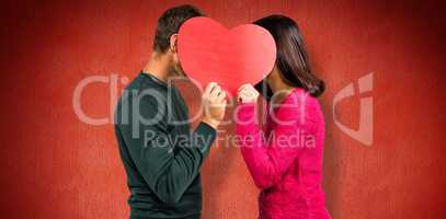 Composite image of couple covering faces with heart shape