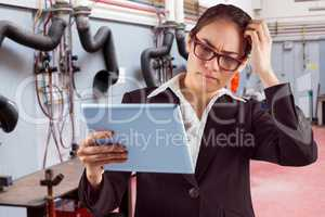 Composite image of thinking businesswoman looking at tablet pc