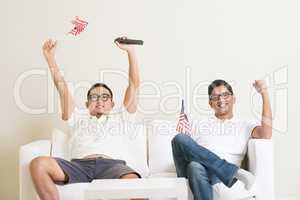 Malaysian men watching sports on tv