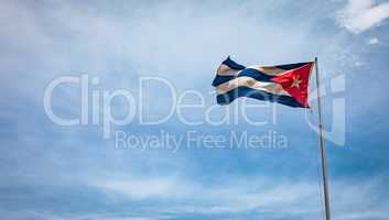 Cuban flag flying in the wind on a backdrop of blue sky.