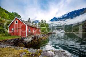 Norway landscape, the house on the shore of the fjord in the bac