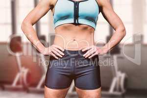 Composite image of midsection of powerful woman with hands on hi