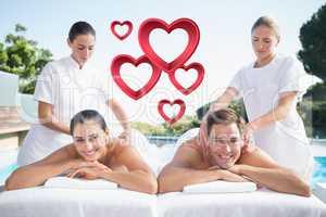 Composite image of smiling couple enjoying couples massage pools