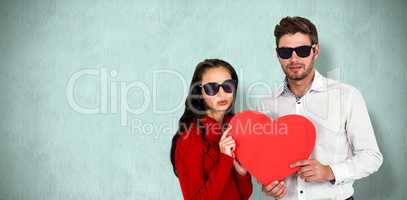 Composite image of portrait of couple with sunglasses holding pa