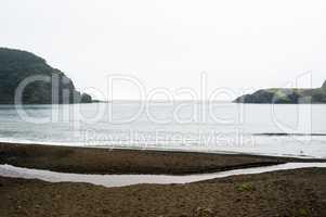 Wet beach in small bay between coastline