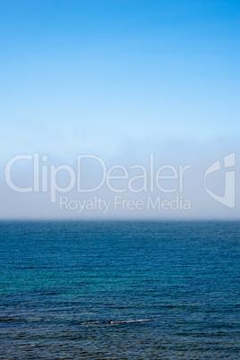 Fog low over wavy water under blue sky