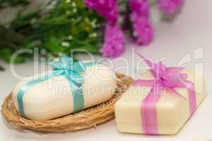 Two pieces of soap with a basket with a bow and flowers