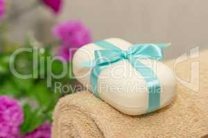 Soap with blue ribbin bow on towel and witn purple flowers on th