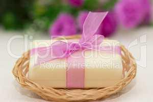 Big piece of beige soap in busket, witn purple bow, flowers on b