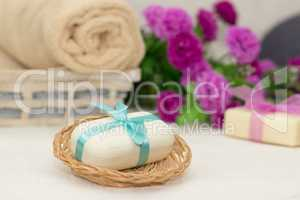 Big piece of beige soap in busket, witn blue  bow, flowers and t