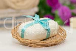 Big piece of beige soap in busket, witn blue bow, flowers on bac