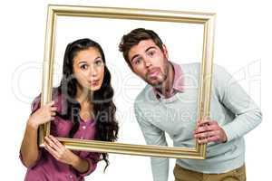 Couple sticking out tongue while holding picture frame