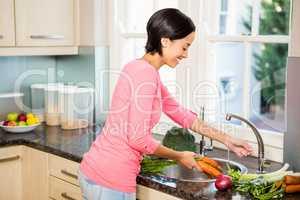 Smiling brunette washing carrots