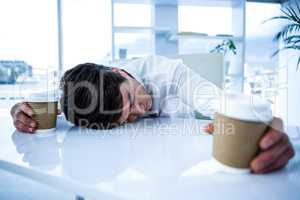 Sleeping businessman holding goblet of coffee