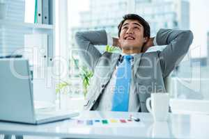 Relaxing asian businessman at his desk