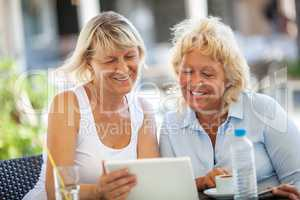 Two women friends using tablet PC in outdoor cafe