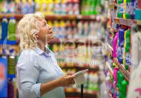 Woman with pad shopping for household detergents