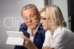 Mature businesspeople working with tablet PC