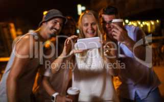 Happy friends making phone selfie at night