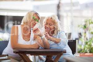 Mature women using smart watch in street cafe