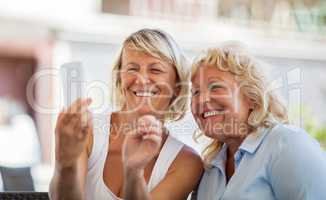 Modern mature women making happy mobile selfie
