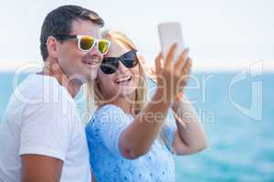 Happy summer selfie of young couple in sunglasses