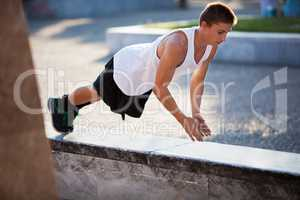 Teenager performing push-ups outdoor in city