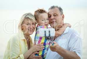 Grandparents and grandson making phone selfie