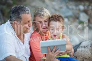 Grandparents and grandson with tablet PC outdoor