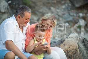 Happy boy with cell phone and grandparents outdoor