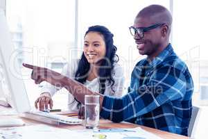 Cheerful businessman discussing with businesswoman over computer