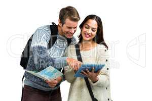 Couple using map and digital tablet while traveling
