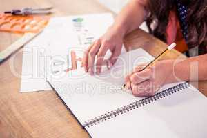 Businesswoman writing in book