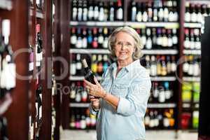 Smiling senior woman choosing wine