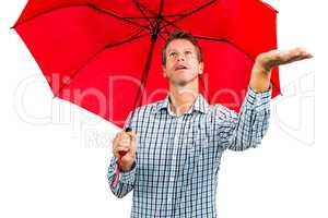 Man checking weather while holding red umbrella