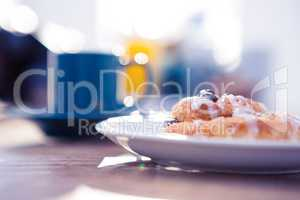 Sweet food served in plate by coffee cup