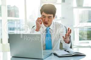 Busy asian businessman working on laptop and calling