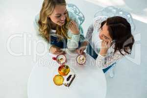 two girls drink coffee