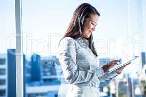 Smiling businesswoman using tablet near the window in office