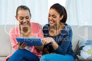 Friends using tablet on sofa
