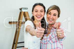 Smiling mother and daughter with thumbs up